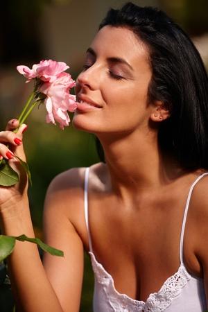 smell: Hermosa mujer disfrutando de aroma de flores de los ojos cerrados en el verano en el jard�n.