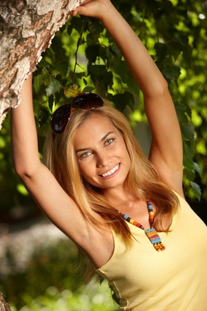 Happy young woman posing by tree in the garden, smiling. Stock Photo - 12174734