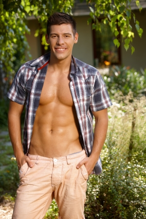 caucasian man: Sexy man smiling with bare chest in the garden at summertime. Stock Photo