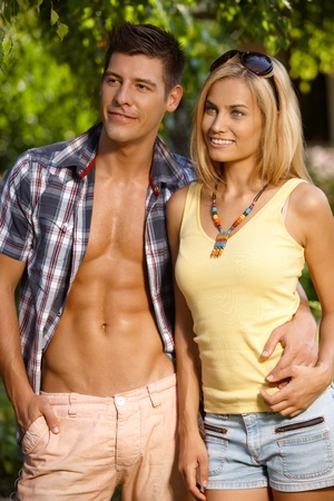 Attractive young smiling couple standing in the green, embracing. photo