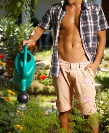 one young man only: Torso of young man watering plants in the garden at summertime.