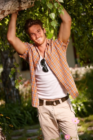 Happy young man posing by tree at summertime. photo