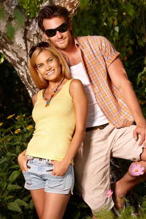 Attractive young couple smiling in the green at summertime. photo