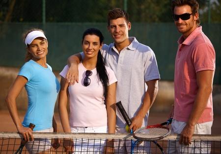 compa�erismo: El compa�erismo feliz de pie en pista de tenis con una sonrisa.