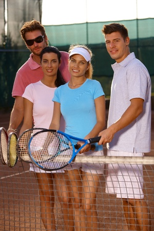 Young friends standing on tennis court, smiling. photo