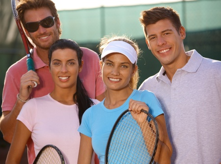 Portrait of smiling young tennis team on tennis court. photo