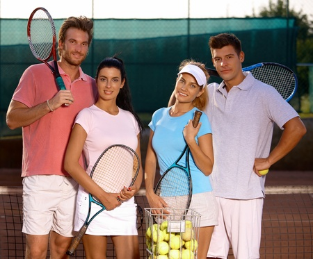 Attractive young couples standing on tennis court, smiling, looking at camera. photo