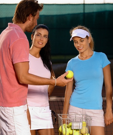 Young people starting tennis game, smiling. photo