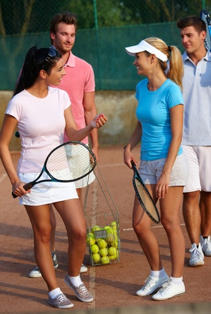 raqueta de tenis: Sonriendo j�venes jugadores de tenis de dobles mixtos preparados. Foto de archivo