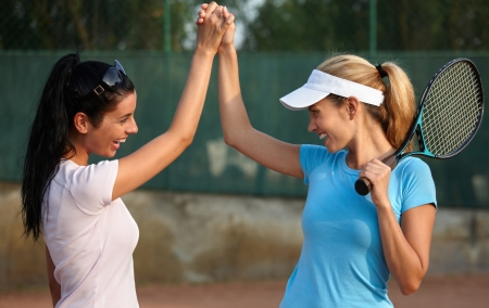 Happy girls playing tennis, shaking hands, smiling. photo