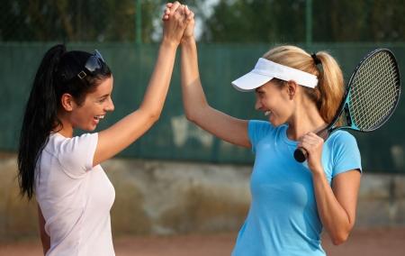 raqueta de tenis: Ni�as felices jugando al tenis, darse la mano, sonriendo.
