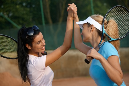 Attractive young girls shaking hands on tennis court, smiling. photo