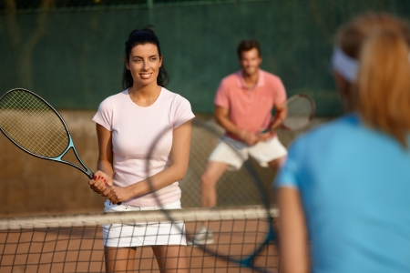 tennis racket: Young people playing tennis, mixed doubles, smiling.