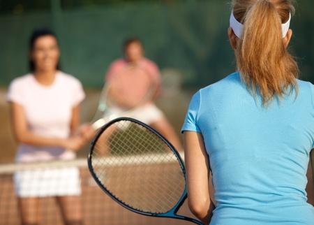 raqueta tenis: Compa��a joven que juega dobles mixtos en la cancha de tenis. Foto de archivo