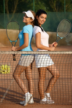 tennis skirt: Attractive young girls posing on tennis court, smiling.
