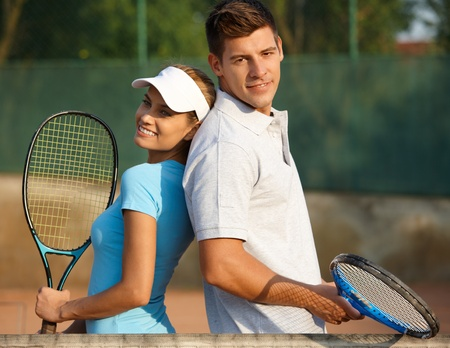 leisure wear: Happy couple posing on tennis court, smiling. Stock Photo