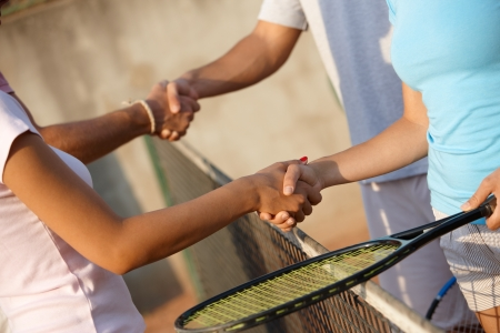Young players shaking hands on tennis court, only hands can be seen. photo
