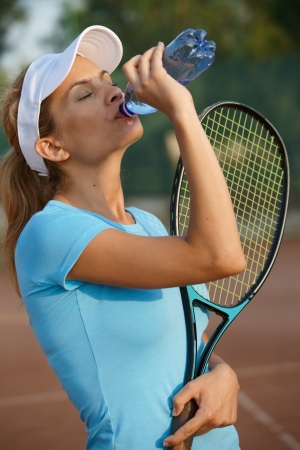 standing water: Attractive young female tennis player drinking water on tennis court. Stock Photo
