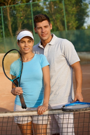 Attractive young couple standing on tennis court, smiling. photo