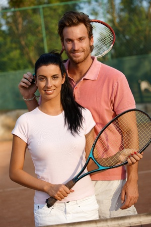 tennis racket: Smiling young couple standing on tennis court, holding tennis racket.