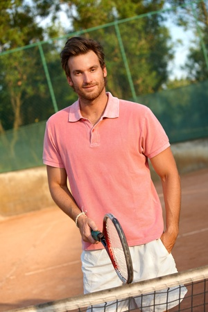 Handsome young male tennis player smiling on tennis court. photo