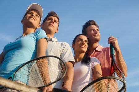 leisure wear: Team of smiling tennis players, photographed from below.