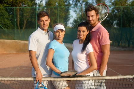 Young couples standing on tennis court, smiling. photo