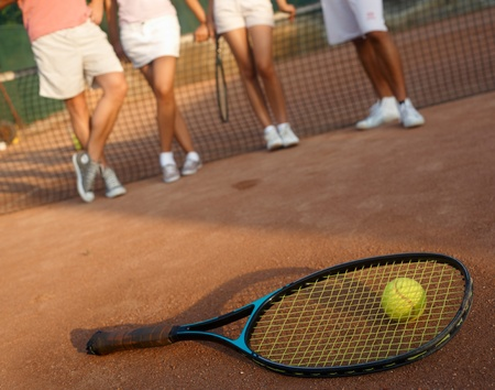 Tennis racket and ball on hard court, players standing in the background, only legs to be seen. photo