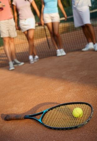 short skirt: Tennis racket and ball on hard court, players at background. Stock Photo
