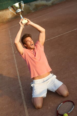Male tennis player shouting victoriously with cup in hand. photo