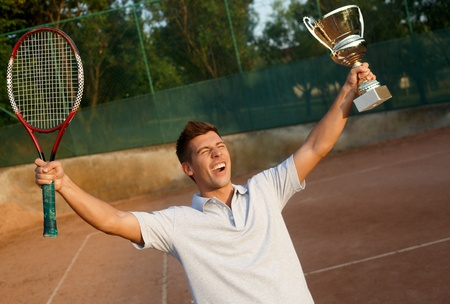 Young male player shouting happily with cup and tennis racket in hands. photo