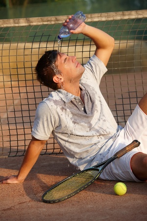 Male tennis player refreshing himself by water, sitting on ground. photo