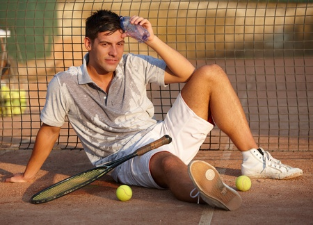 Handsome tennis player sitting on hard court, exhausted, looking at camera. photo