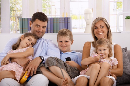 indoor photo: Happy family sitting on sofa at home, smiling, having three children.