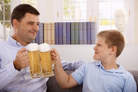 jovenes tomando alcohol: Padre e hijo tomando cerveza, chocando con gafas, sonriente.