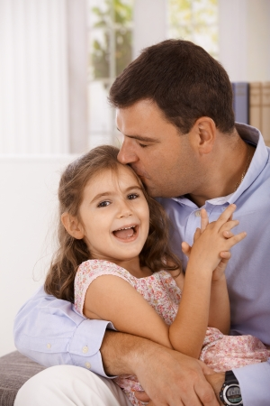 be kissed: Father hugging and kissing little daughter, smiling. Stock Photo
