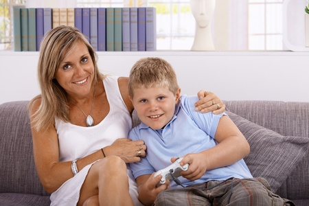 Little boy and mother playing video game, smiling, having fun.