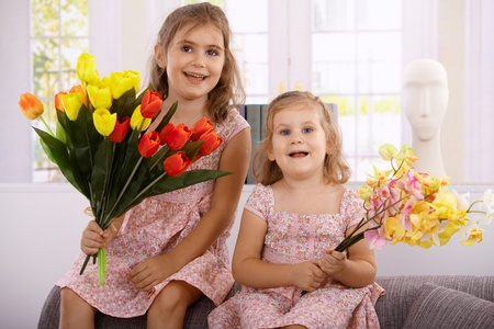 Little girls holding bouquet of flowers, smiling happily at mother's day. Stock Photo - 12471256