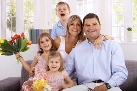 Happy family with three children smiling happily at home, girls holding bouquet of flowers. photo