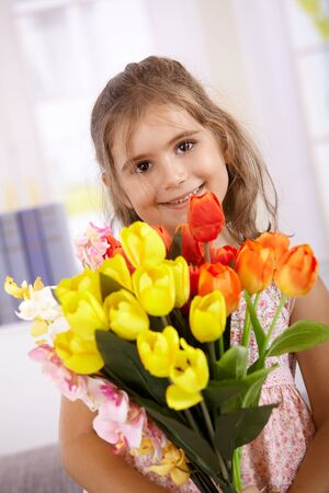 Cute little girl holding bouquet of flowers, smiling on mother's day, looking at camera. photo