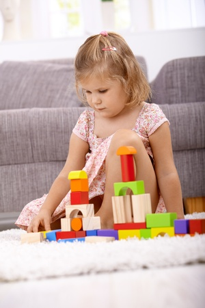 indoor photo: Little girl playing at home with cubes, sitting on floor. Stock Photo
