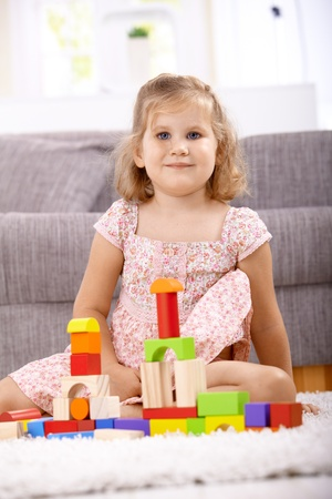 children playing with toys: Smiling little girl playing at home, building tower by cubes, looking at camera.