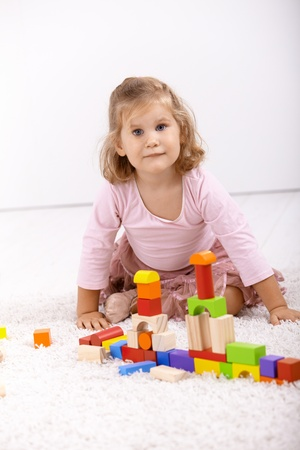 offish: Little girl playing with cubes at home, sitting on floor, looking at camera.