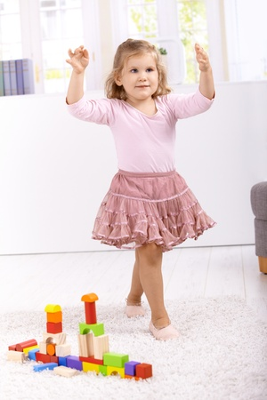 Lovely little ballerina girl playing at home. photo