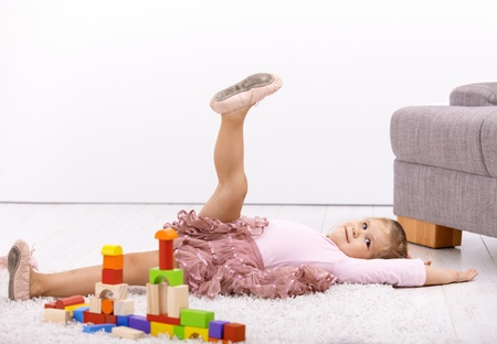 carpet color: Little ballerina girl laying on floor at home, playing, posing.