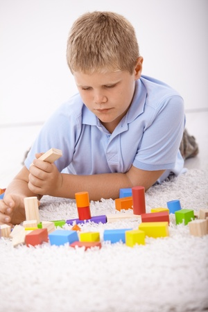 offish: Schoolboy laying on floor at home, playing with cubes. Stock Photo