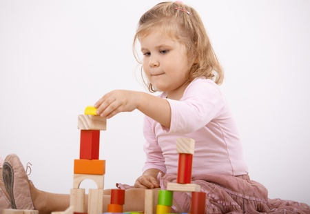 offish: Little girl playing at home, building tower by cubes. Stock Photo