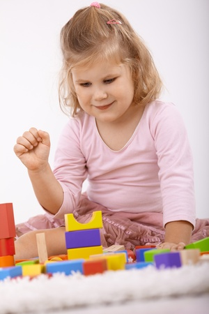 Cute little girl sitting on floor at home, playing with cubes, smiling. photo