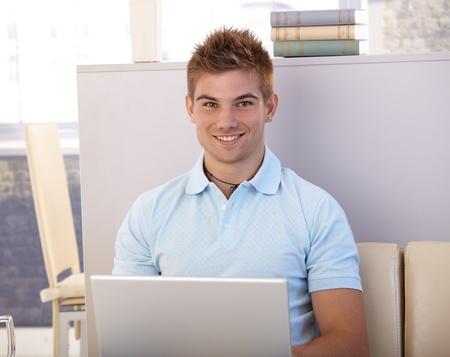 Happy young man sitting at home using laptop computer, smiling at camera. Stock Photo - 12470798