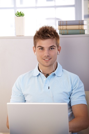 Portrait of casual handsome young guy with laptop computer and earphones, listening to music. photo